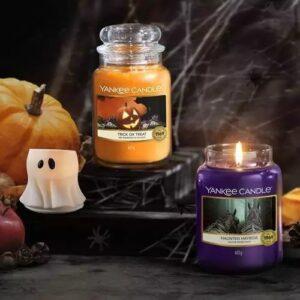 Yankee Candle Halloween Düfte, dekorativ dargestellt im Grusel Look mit Spinnenweben, im Detail Haunted Hayride und Trick Or Treat 623g, daneben auf der Linken Seite ein Votivkerzenhalter in Form eines Geistes