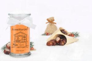JuwelKerze Heiße Maronen (die Duftkerze) dekorativ in Szene gesetzt vor Kastanien und es schneit ganz leicht
